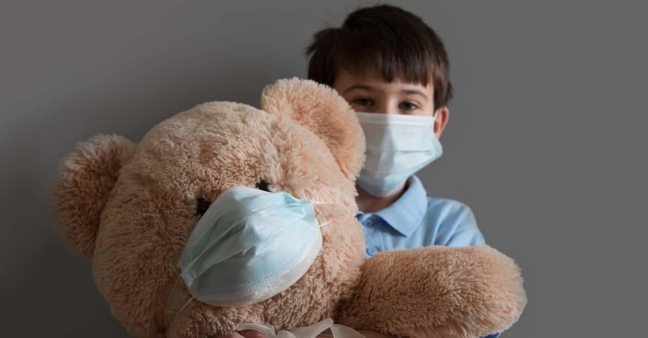 Boy with teddy bear, both wearing masks